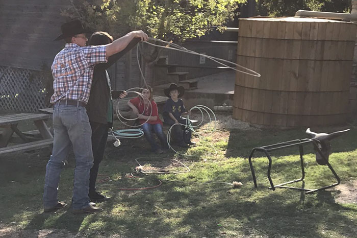 Man teaching youth how to lasso