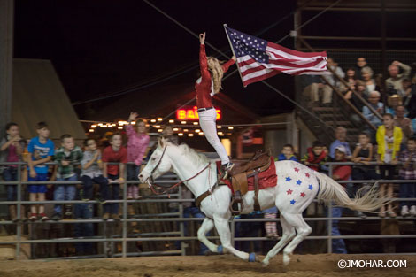 Rider standing on horse holding a US flag